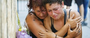 Two friends of Toronto shooting victim Reese Fallon cry and hold each other.
